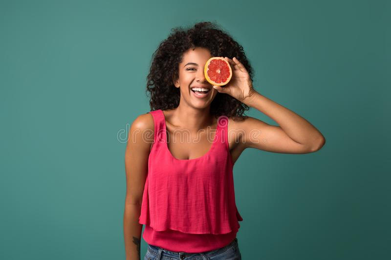 Happy african-american woman holding half of grapefruit stock photo