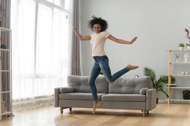 Happy African American woman jumping in living room, celebrating success royalty free stock photos