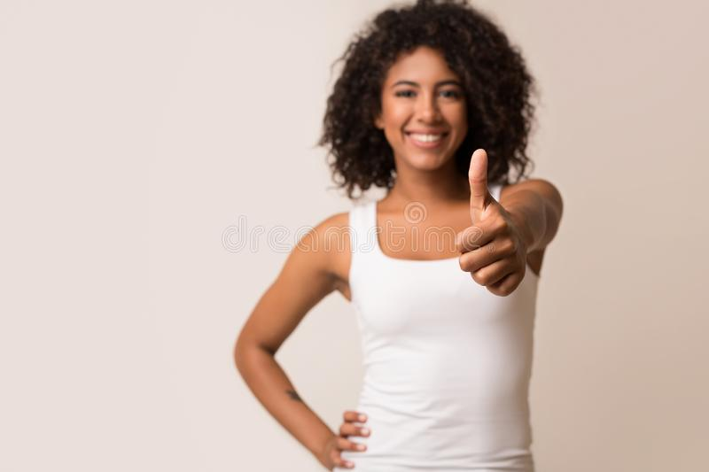 Happy african-american woman showing thumb up on background stock images