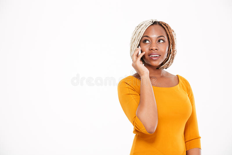 Happy african american woman standing and talking on cell phone royalty free stock images