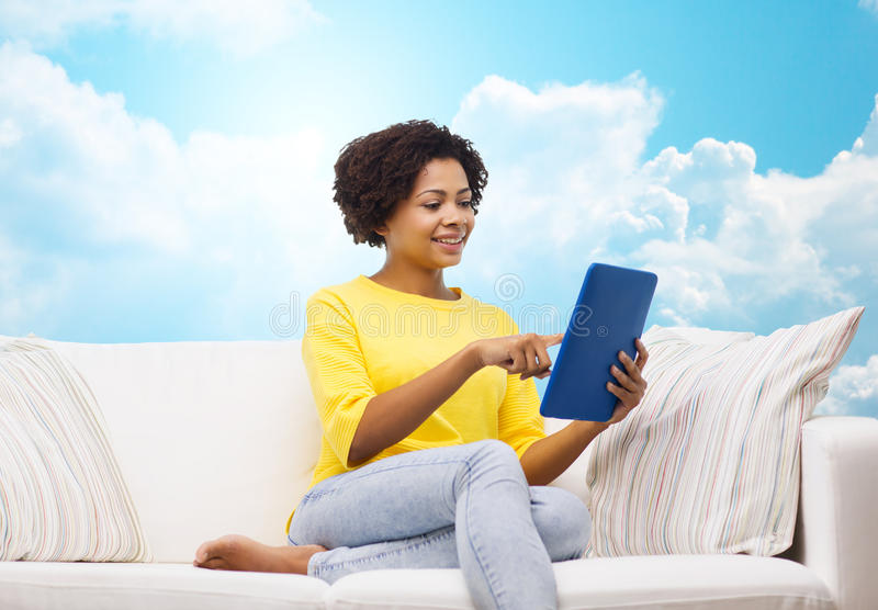 Happy african american woman with tablet pc stock image