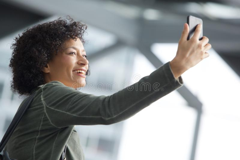 Happy african american woman taking selfie. Side portrait of happy african american woman taking selfie stock photo