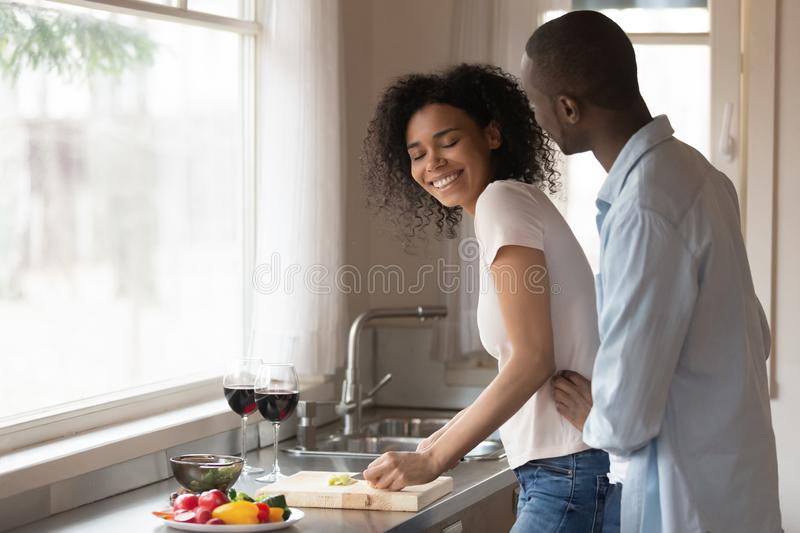Happy biracial couple hug cooking together in kitchen. Happy african American young couple hug in kitchen cooking romantic dinner together, smiling biracial stock photography