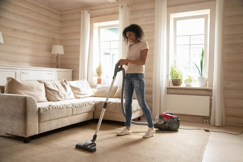 Smiling biracial woman cleaning carpet using vacuum cleaner royalty free stock photography
