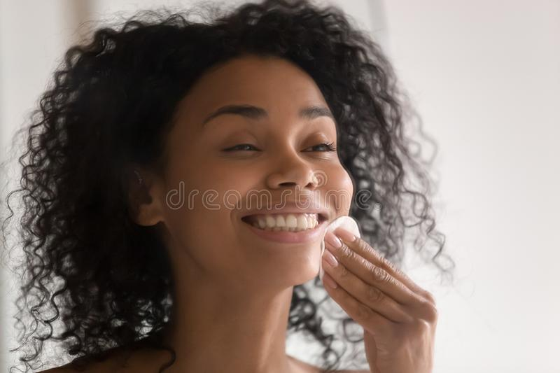 Happy african american young woman using disposable cotton pads. stock images