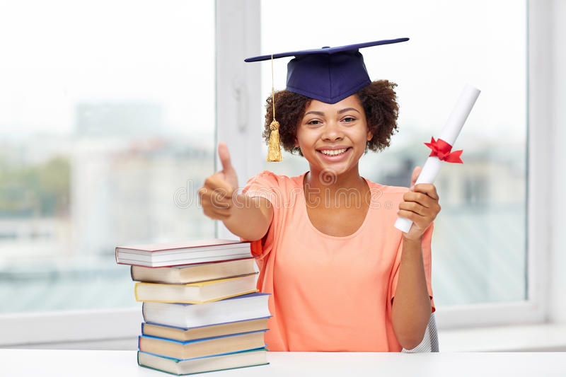 Happy african bachelor girl with books and diploma. Education, school, graduation, gesture and people concept - happy smiling african american student girl in stock photography