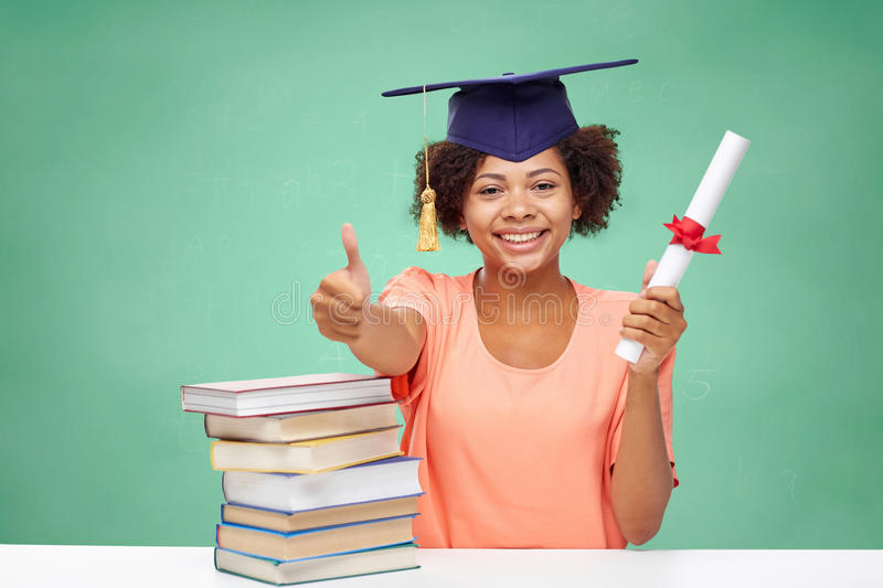 Happy african bachelor girl with books and diploma. Education, school, graduation, gesture and people concept - happy smiling african american student girl in stock photos