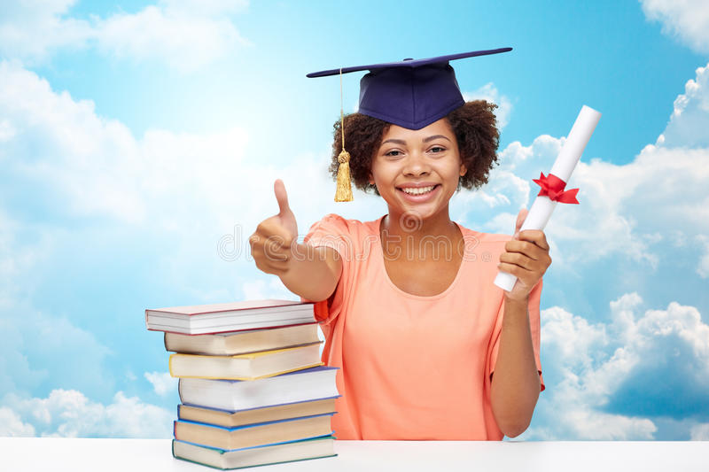 Happy african bachelor girl with books and diploma. Education, school, graduation, gesture and people concept - happy smiling african american student girl in royalty free stock photos