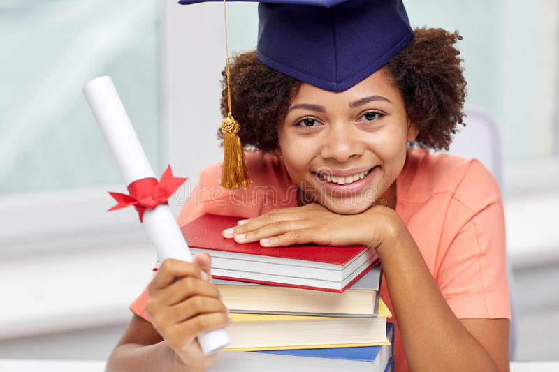 Happy african bachelor girl with books and diploma. Education, school, graduation and people concept - happy smiling african american student girl in bachelor stock photo