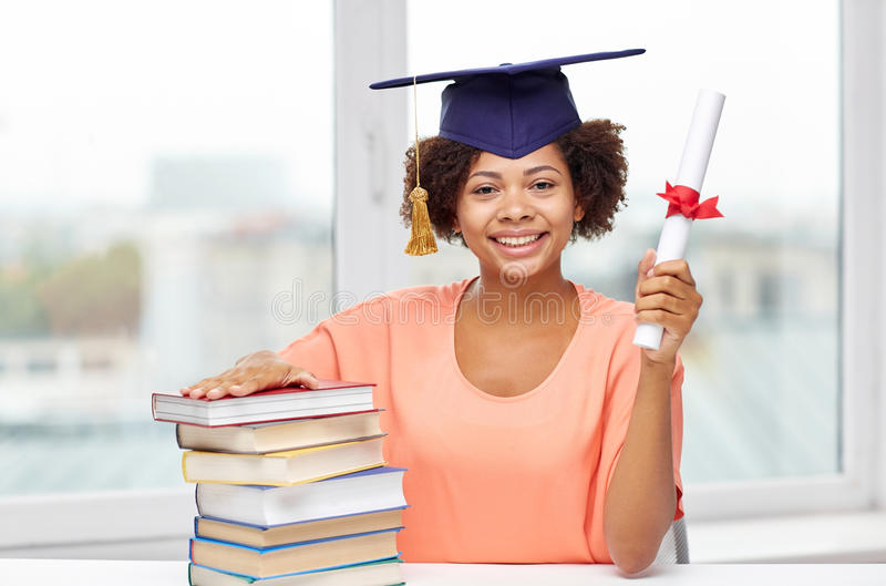 Happy african bachelor girl with books and diploma. Education, school, knowledge, graduation and people concept - happy smiling african american student girl in royalty free stock photo