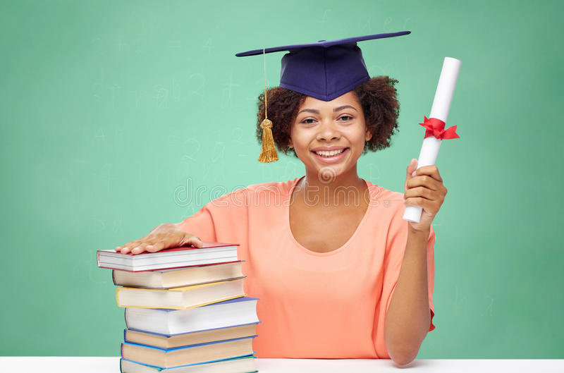 Happy african bachelor girl with books and diploma. Education, school, knowledge, graduation and people concept - happy smiling african american student girl in stock images