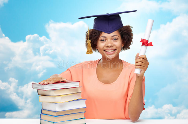 Happy african bachelor girl with books and diploma. Education, school, knowledge, graduation and people concept - happy smiling african american student girl in royalty free stock photography