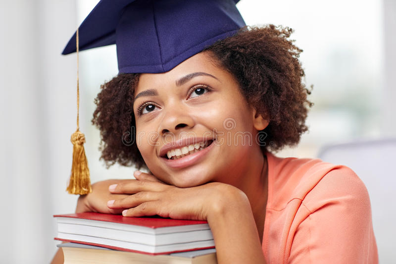 Happy african bachelor girl with books at home. Education, school, knowledge, graduation and people concept - happy smiling african american student girl in stock photography