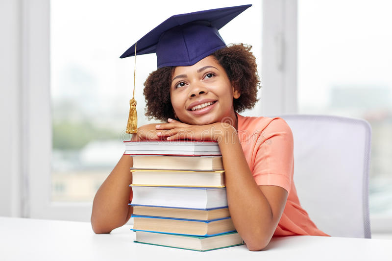 Happy african bachelor girl with books at home royalty free stock photos