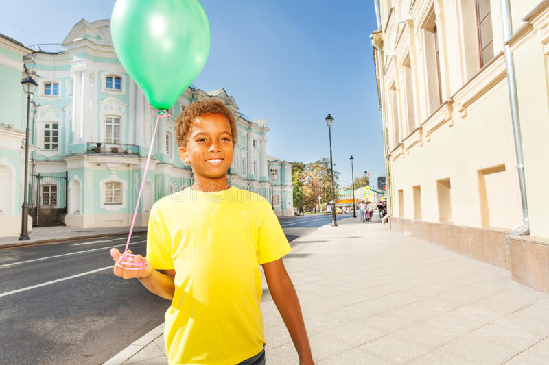 Happy African boy in yellow T-shirt with balloon stock image