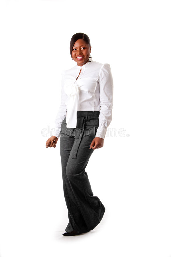 Happy African business woman. Beautiful African American business woman with attitude dressed in a white shirt and gray pants standing, dancing happy, isolated stock photos