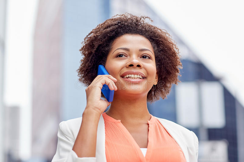 Happy african businesswoman calling on smartphone stock photo