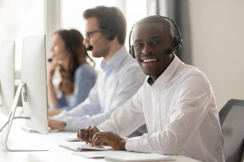 Happy african call center agent in headset posing at workplace stock photos