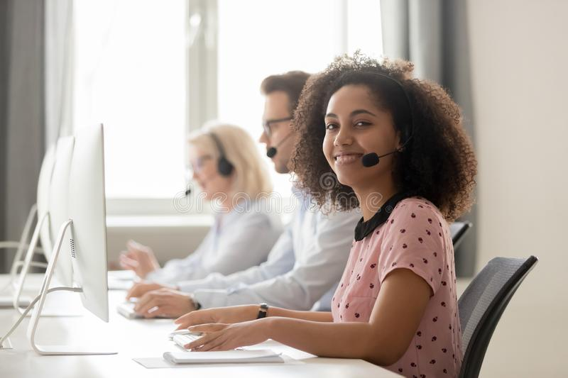 Happy african call center operator wearing headset looking at camera royalty free stock images