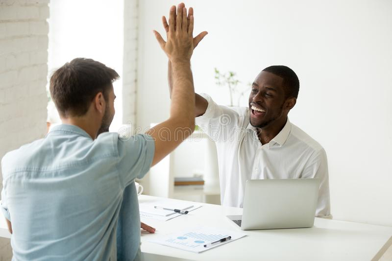 Happy african and caucasian businessmen giving high five in offi. Ce, diverse motivated colleagues partners team celebrating good work result or business success royalty free stock photography