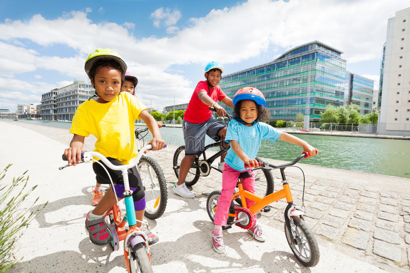 Happy African children cycling along the river stock image