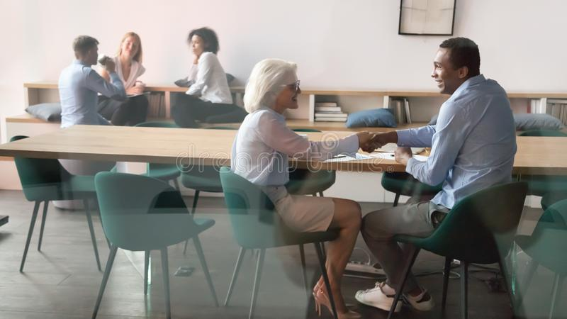 Happy african client handshaking thanking aged manager making business deal. Happy african american client handshaking thanking aged female manager making royalty free stock photo