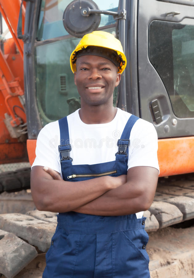 Happy african construction worker with crossed arms and red excavator. Happy african construction worker with crossed arms laughing at camera with red excavator royalty free stock images