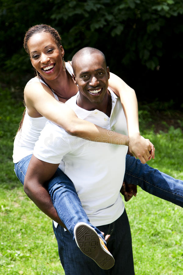Happy African couple. Beautiful happy smiling laughing African American couple piggyback playing in the park, woman hugging man, wearing white shirts and blue