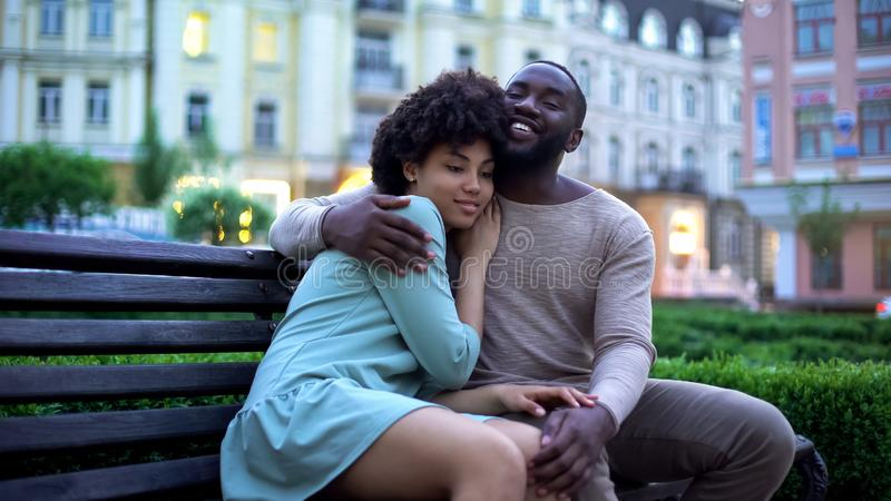 Happy african couple cuddling on bench at sunset, date in city park, closeness. Stock photo royalty free stock photos