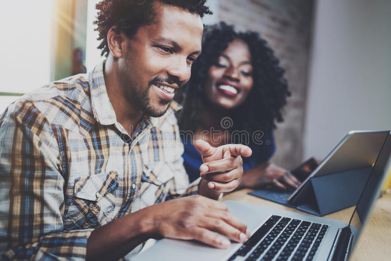 Happy African couple having rest at a home: black man sitting at the table,pointing finger to laptop,looking through royalty free stock photos