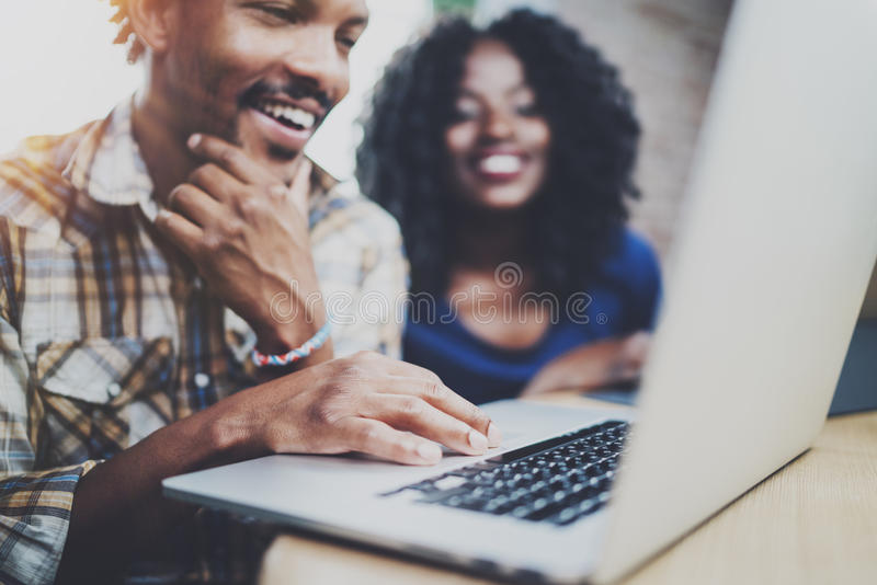 Happy African couple having rest at a home: black man sitting at the table,using laptop and laughing,looking through stock image
