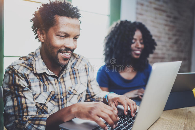 Happy African couple having rest at a home: black man sitting at the table,using laptop and laughing,looking through royalty free stock photography