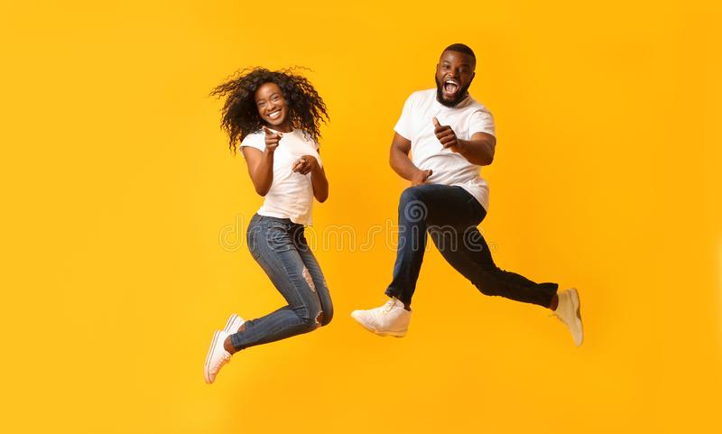 Happy african couple jumping in the air. Carefree Black Millennial Couple Jumping In The Air, girl pointing at camera, guy showing thumbs up, yelllow background stock image