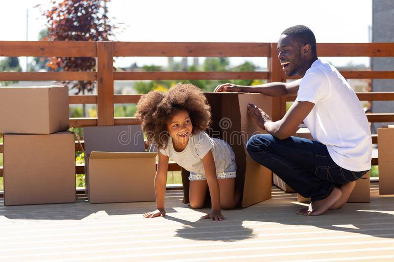 Happy african dad and kid playing with boxes on porch royalty free stock photo