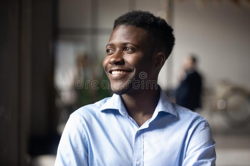Happy African ethnicity businessman standing in modern workspace feels satisfied stock photography