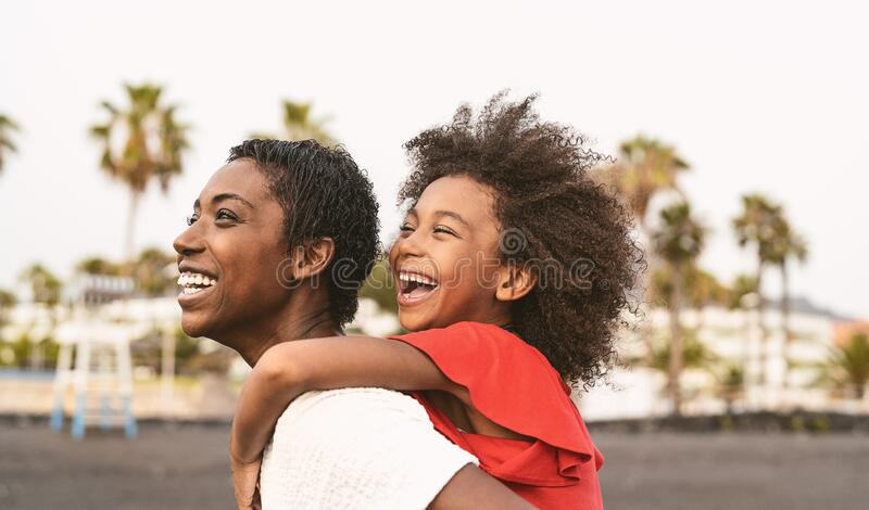 Happy African family on the beach during summer holidays - Afro American people having fun on vacation time. Parents love and travel lifestyle concept royalty free stock photography
