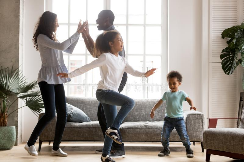 Happy african family and children having fun dancing at home. Happy african american family and funny active children having fun dancing together at new home stock photography