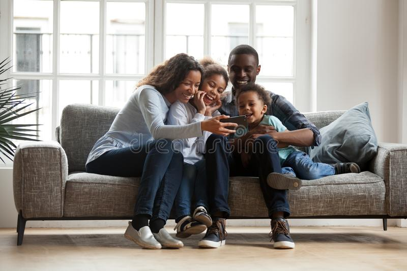 Happy african family with 2 children having fun with gadget stock photography