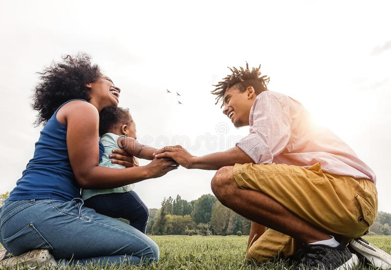 Happy African family having fun in public park - Mother, father and daughter enjoying together during a weekend sunny day outdoor royalty free stock photos