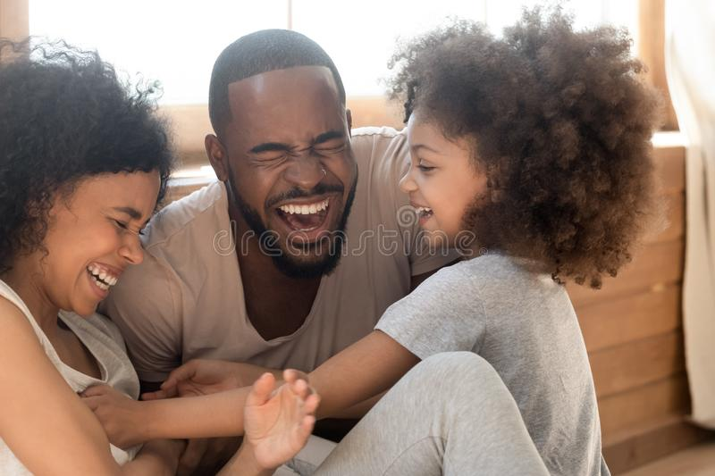 Happy african family with kid daughter tickling laughing together stock image