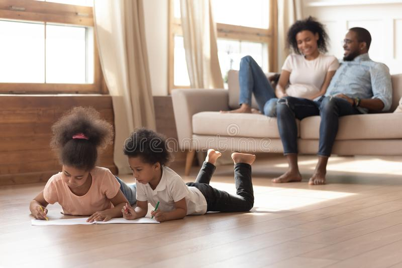 Happy african family with kids leisure activities in living room. Happy african american family with kids leisure lifestyle activities in modern living room royalty free stock image