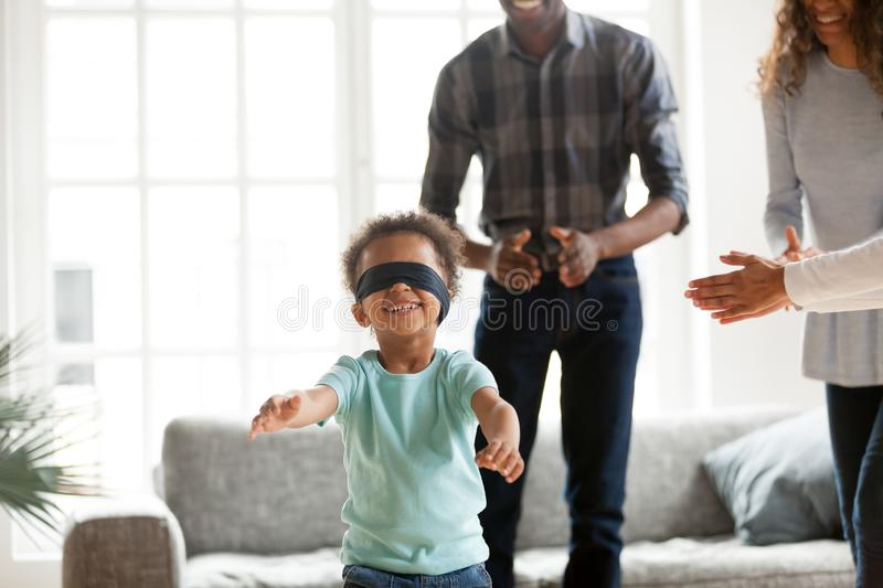 Happy African family playing hide and seek at home royalty free stock photography