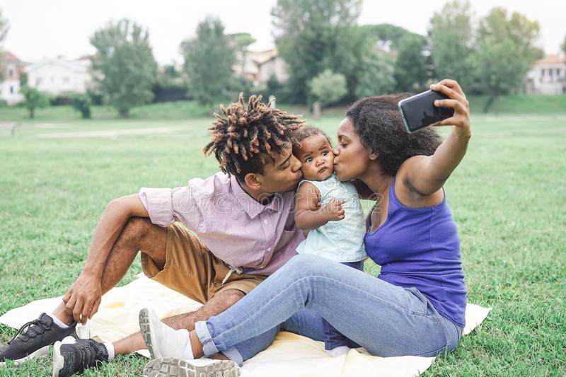 Happy african family taking a selfie with mobile smart phone camera in a public park outdoor royalty free stock images