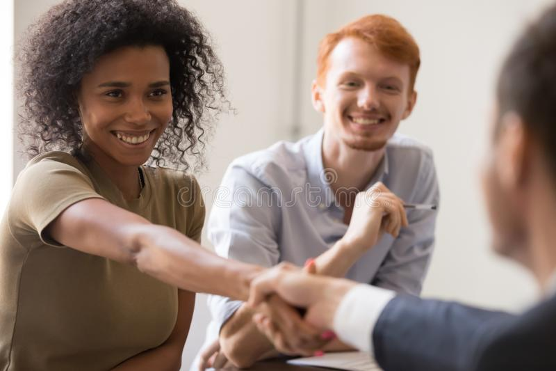 Happy african hr handshake candidate at team meeting job interview. Happy african female hr handshake candidate client new worker welcoming at team meeting job royalty free stock photos