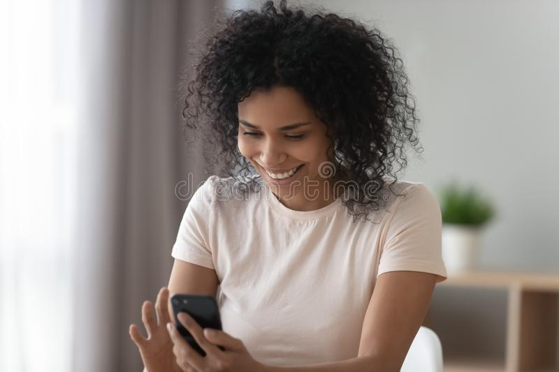 Happy african girl holding cellphone using smartphone social media app stock image