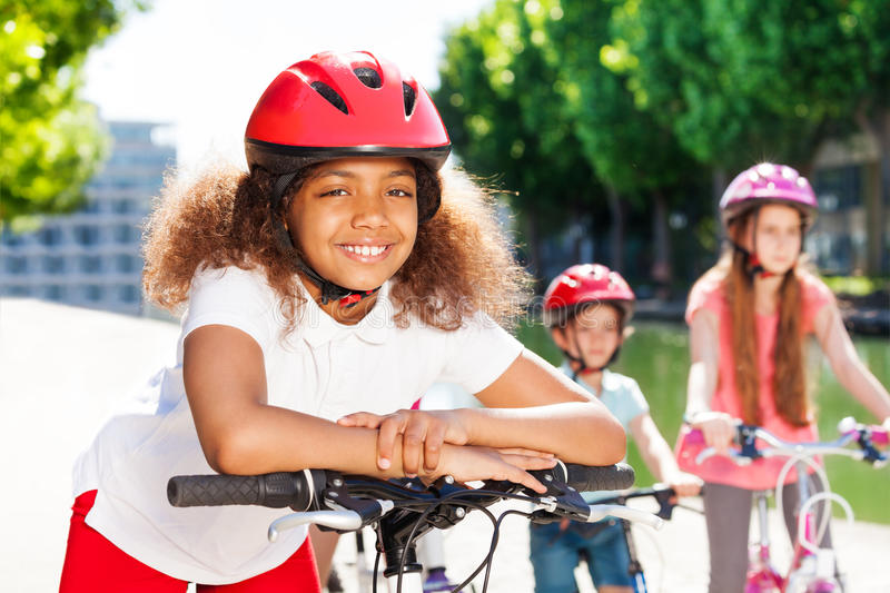 Happy African girl riding bicycle in summer city stock image