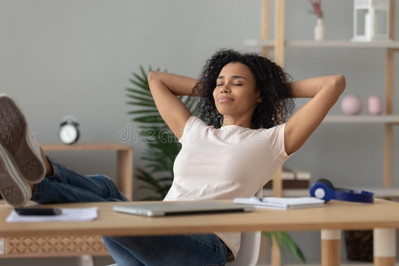 Happy african girl student relaxing finished study sit at desk royalty free stock photography