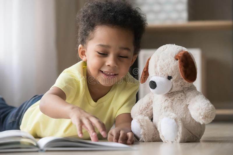 Happy african little boy playing alone reading book to toy stock image
