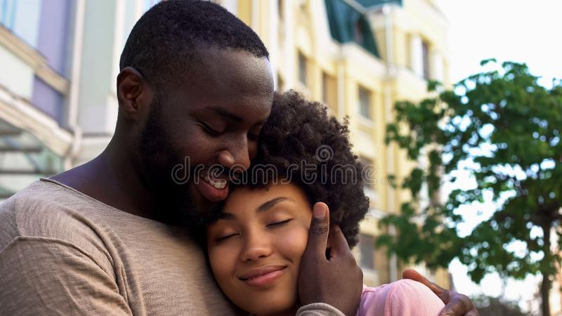 Happy african male hugging girlfriend, loving couple, outdoor romantic date royalty free stock image