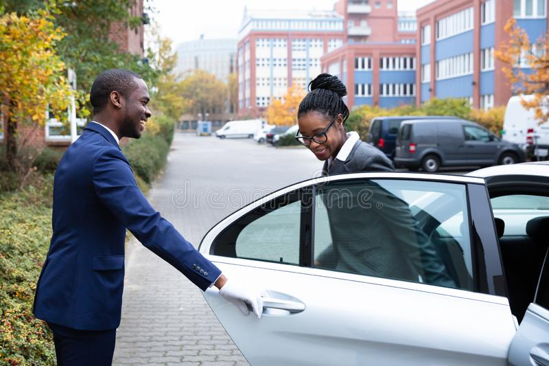Valet Opening Door For Businesswoman Getting Out Of A Car royalty free stock photos